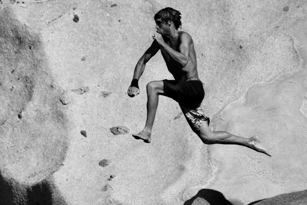 homme qui saute d'en haut d'un rocher dans la mer