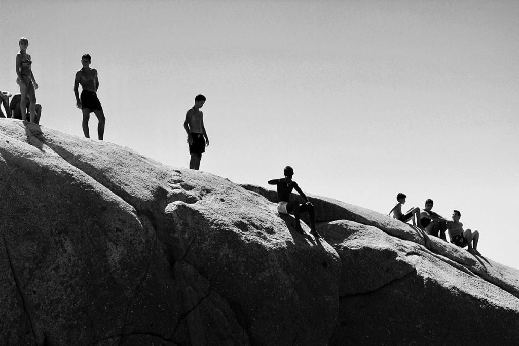 adolescents qui s'apprêtent à sauté du rocher dans la mer